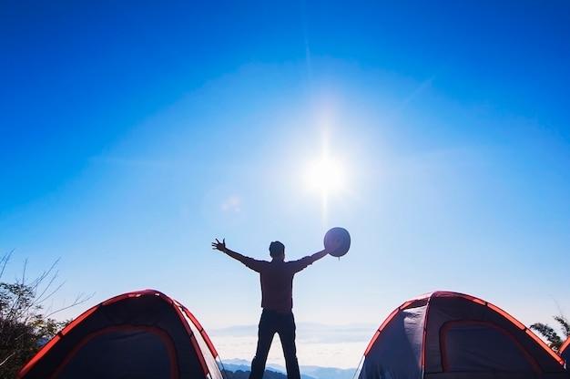 El hombre feliz acampa de pie y levanta la mano sosteniendo su sombrero en la montaña por la mañana Foto gratis