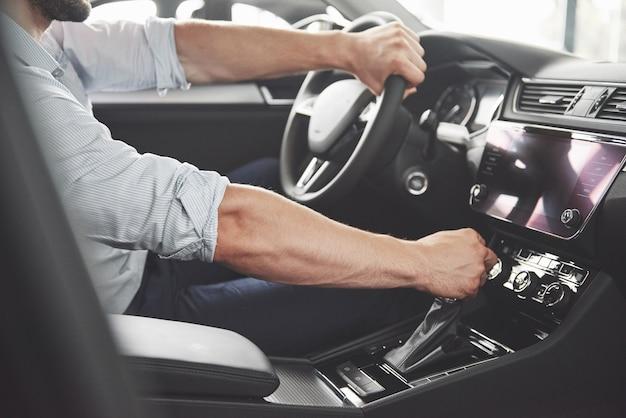 Hombre feliz barbudo atractivo en buen coche. Foto gratis