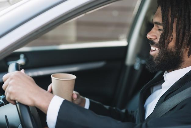 Hombre feliz conduciendo vista lateral Foto gratis