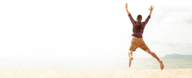 Hombre feliz enérgico saltando en la playa en vacaciones de verano Foto Premium