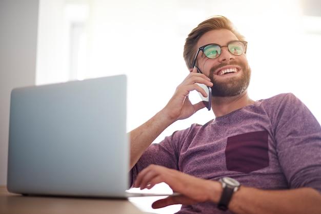 Hombre feliz haciendo negocios en la oficina en casa Foto gratis