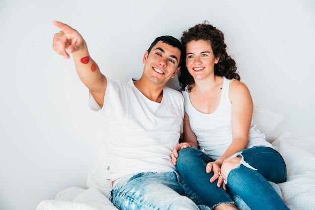 Hombre feliz joven con la mano estirada y la mujer que se sientan en cama Foto gratis