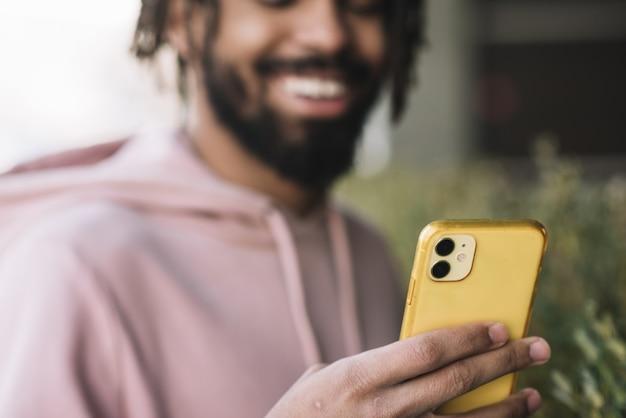 Hombre feliz mirando el teléfono Foto gratis