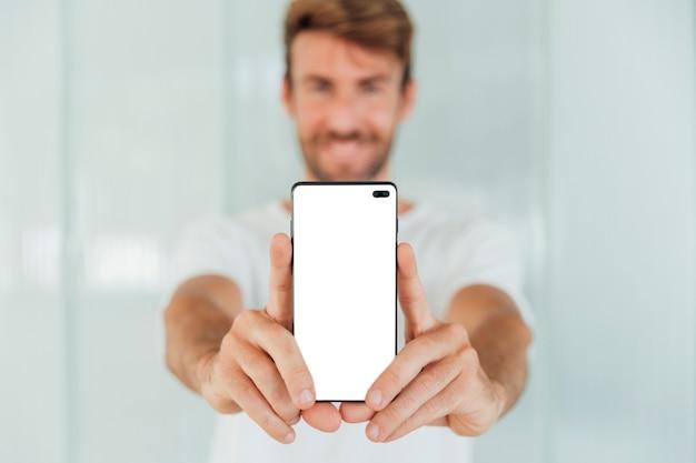 Hombre feliz mostrando teléfono inteligente con maqueta Foto gratis