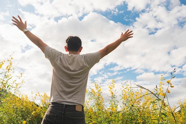 Hombre feliz en la naturaleza de la flor de campo amarillo y el cielo brillante nube blanca Foto gratis