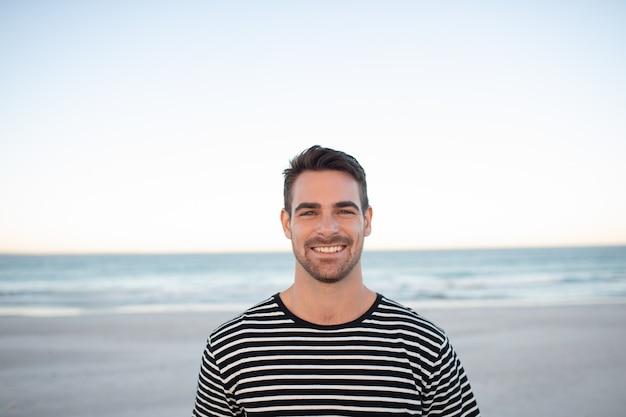 Hombre feliz de pie en la playa Foto gratis
