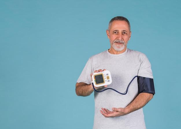 Hombre feliz que muestra los resultados de la presión arterial en tonómetro eléctrico Foto gratis