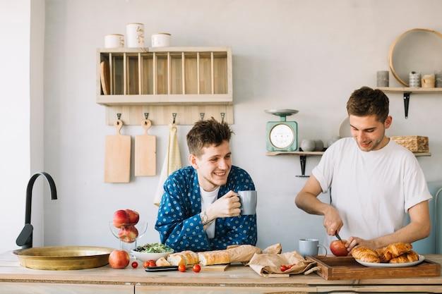 Hombre feliz que sostiene la taza de café y su manzana del corte del amigo en tajadera en cocina Foto gratis