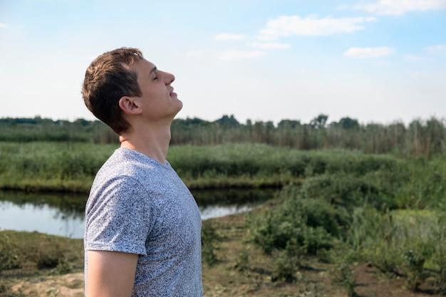 Hombre feliz respirando profundamente aire fresco al aire libre con el lago y el campo en el fondo Foto Premium