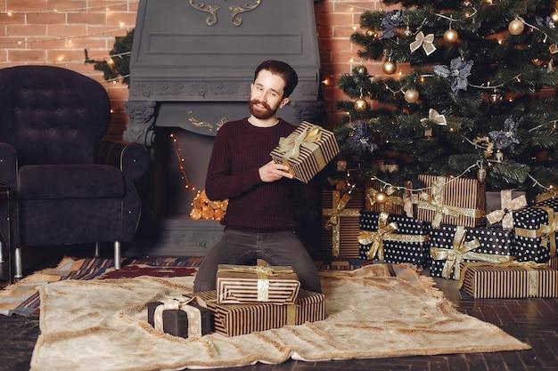 Hombre feliz en suéter rojo. chico frente a la chimenea. hombre en el fondo del árbol de navidad. Foto gratis