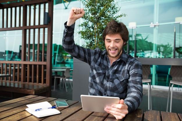Hombre feliz usando tableta y celebrando logros en café Foto gratis