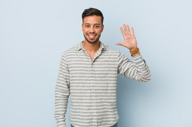 Hombre filipino hermoso joven que sonríe alegre mostrando el número cinco con los dedos. Foto Premium