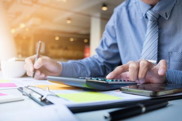 Hombre de finanzas de negocios calculando los números de presupuesto, facturas y asesor financiero trabajando. Foto gratis