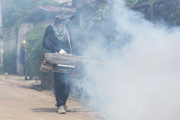 Un hombre fogging químico para eliminar el mosquito Foto Premium