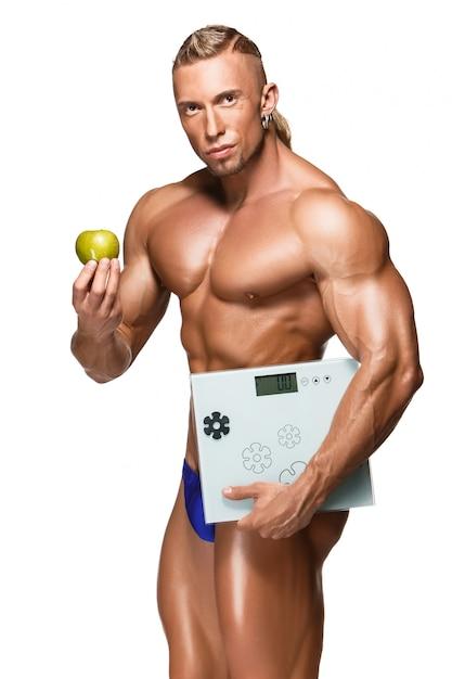 Hombre en forma y saludable cuerpo sosteniendo una manzana fresca, aislado sobre fondo blanco. Foto gratis