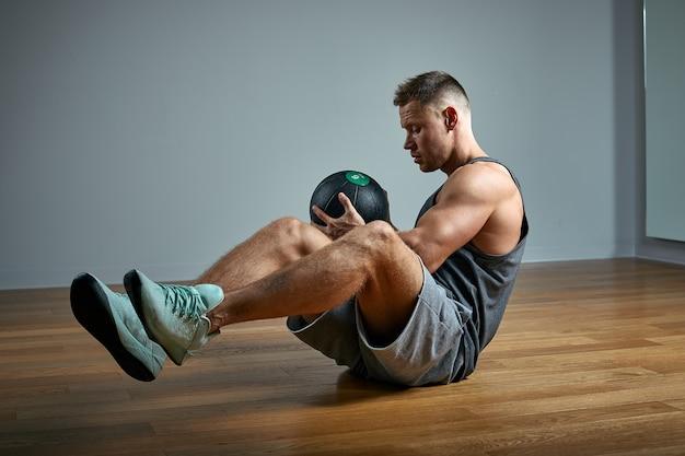 Hombre fuerte haciendo ejercicio con balón med. foto del físico perfecto del hombre en la pared gris. fuerza y motivación. Foto Premium