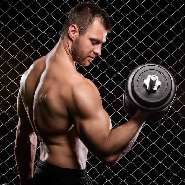 Hombre fuerte y sus músculos con pesas Foto gratis