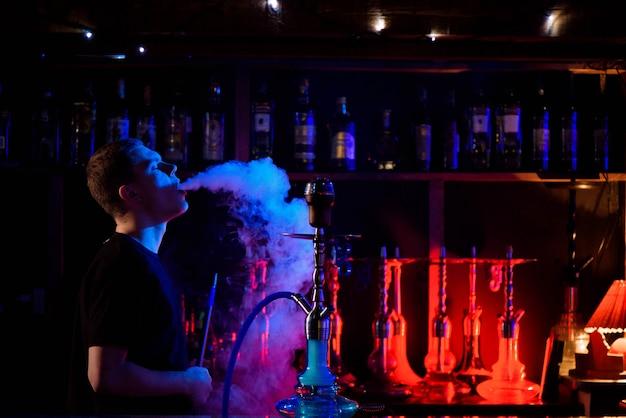 Hombre fumando pipa de narguile tradicional y exhalando humo en la cafetería hookah. Foto Premium