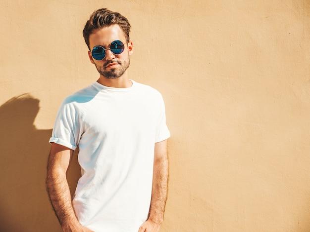 Hombre con gafas de sol con camiseta blanca posando Foto gratis