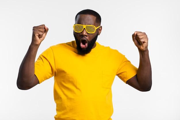 Hombre con gafas de sol celebrando Foto gratis