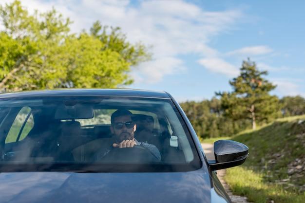 Hombre con gafas de sol conduciendo coche Foto gratis