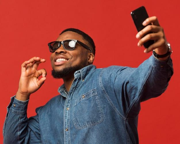 Hombre con gafas de sol tomando selfie Foto Premium