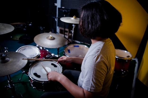 Hombre grabando música en batería en estudio Foto gratis