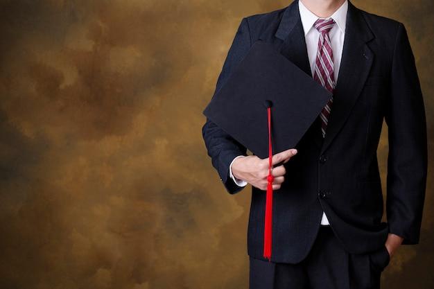 Hombre graduado que sostiene el casquillo negro de la graduación. copyspace Foto Premium