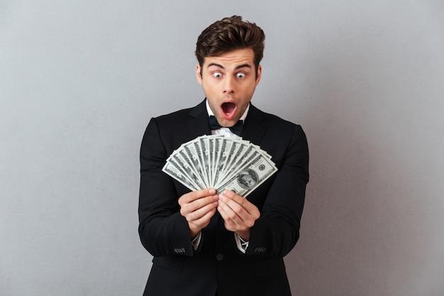 Hombre gritando en traje oficial con dinero. Foto gratis