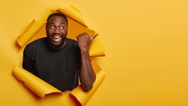 Hombre guapo alegre con amplia sonrisa dentuda, apunta a un lado, se encuentra en un agujero de papel rasgado, viste ropa negra. Foto gratis