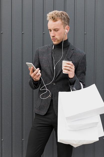 Hombre guapo con auriculares cerca de una pared gris Foto gratis