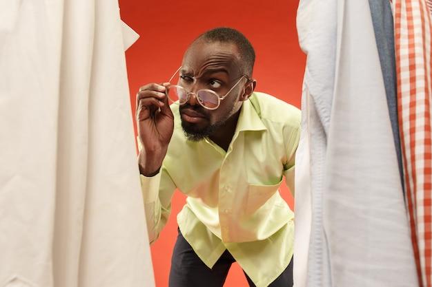 Hombre guapo con barba eligiendo camisa en una tienda Foto gratis