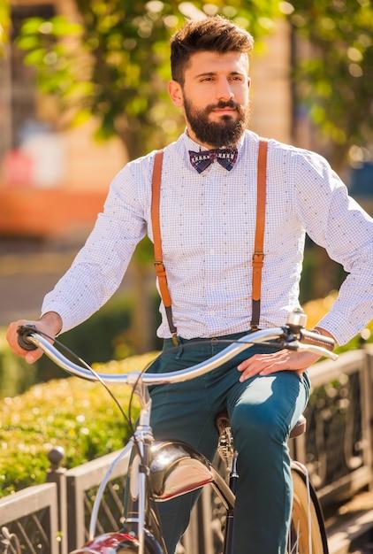 Hombre guapo con barba montando una bicicleta. Foto Premium