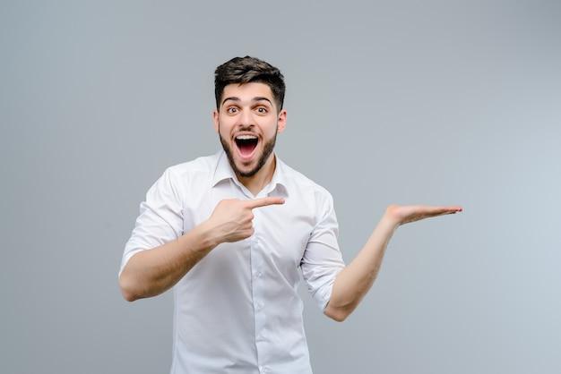Hombre guapo con barba que señala el dedo en copyspace en mano aislado Foto Premium