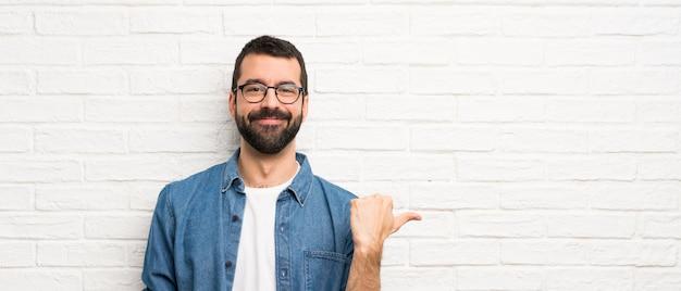 Hombre guapo con barba sobre pared de ladrillo blanco apuntando hacia un lado para presentar un producto Foto Premium