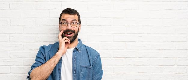 Hombre guapo con barba sobre pared de ladrillo blanco con sorpresa y expresión facial conmocionada Foto Premium