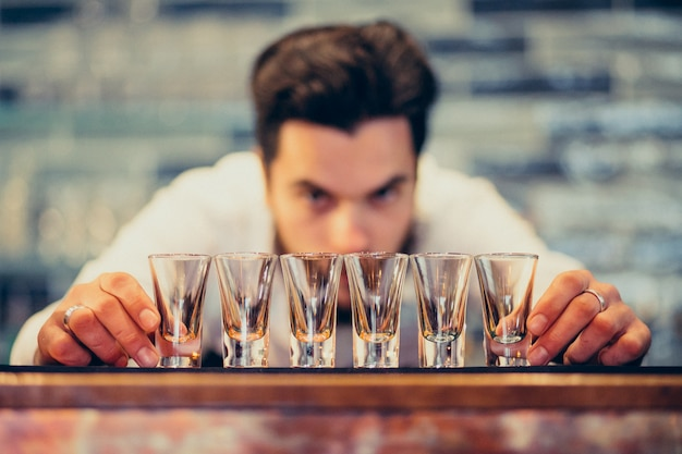 Hombre guapo barman haciendo bebidas y cócteles en un mostrador Foto gratis