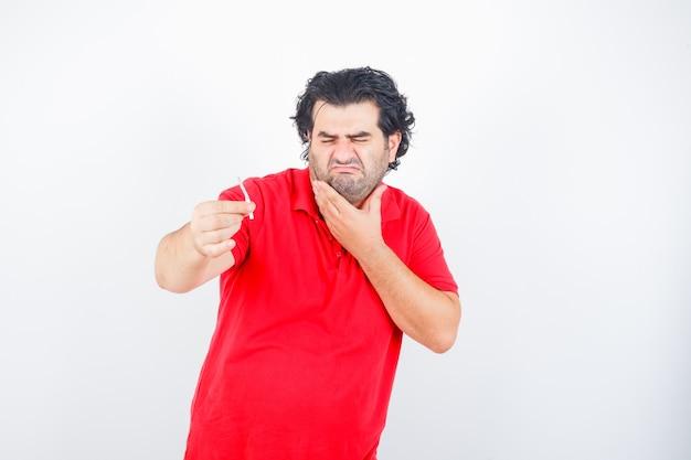 Hombre guapo en camiseta roja sosteniendo un cigarrillo, sosteniendo la mano en el cuello, haciendo muecas y mirando disgustado, vista frontal. Foto gratis