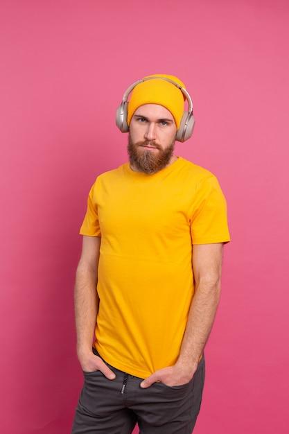 Hombre guapo en casual escuchando música con auriculares aislado sobre fondo rosa Foto gratis