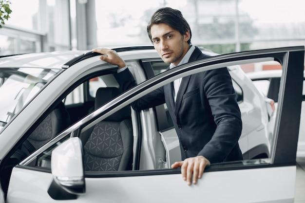 Hombre guapo y elegante en un salón del automóvil Foto gratis