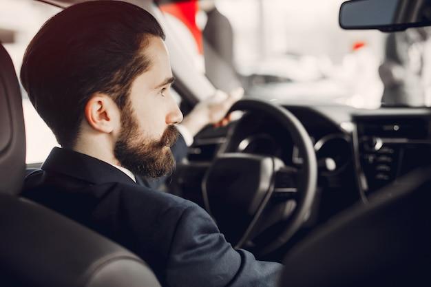 Hombre guapo y elegante en un salón de autos. Foto gratis
