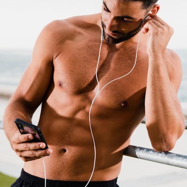 Hombre guapo escucha música al aire libre mientras entrena Foto gratis