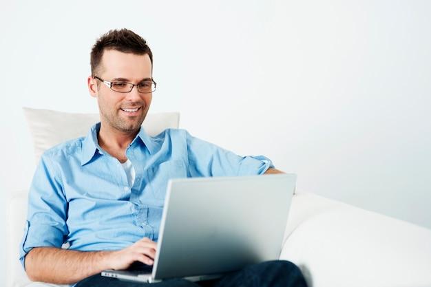 Hombre guapo con gafas usando laptop en sofá Foto gratis