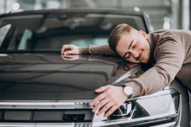 Hombre guapo joven abrazando un coche en una sala de exposición de automóviles Foto gratis