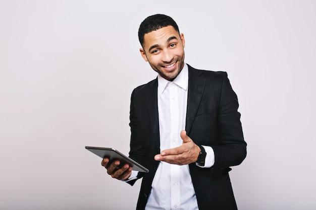 Hombre guapo joven elegante en camisa blanca, chaqueta negra, con tableta sonriendo. logra el éxito, gran trabajo, expresando verdaderas emociones positivas, empresario, trabajador inteligente. Foto gratis