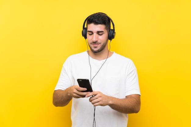 Hombre guapo joven escuchando música con un móvil en la pared amarilla Foto Premium