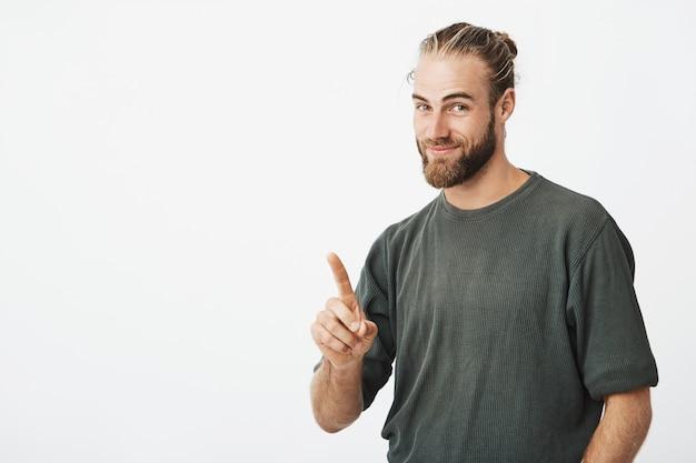 Hombre guapo joven inconformista apuntando con el dedo Foto gratis
