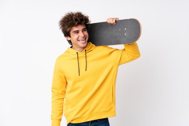 Hombre guapo joven patinador sobre pared blanca aislada Foto Premium