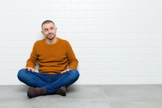 Hombre guapo joven preguntándose, pensando pensamientos e ideas felices, soñando despierto, mirando de lado sentado en el suelo Foto Premium