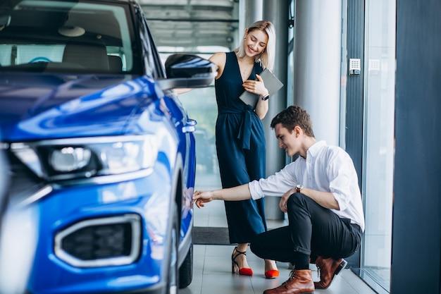 Hombre guapo joven que elige un coche en una sala de exposición de automóviles Foto gratis